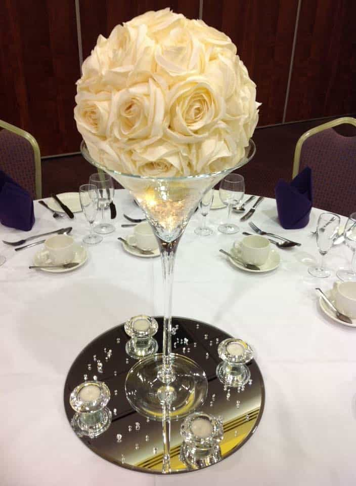 Wedding table centrepiece martini vase with a ball of flowers sitting on the top
