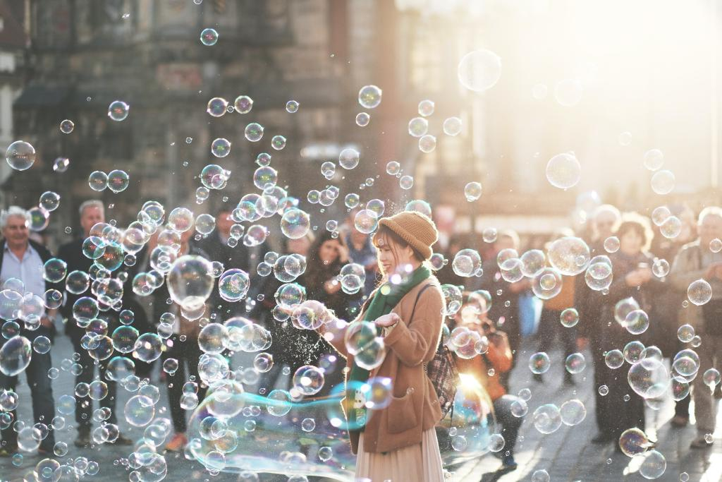 Woman standing in many bubbles on a nice day outside.