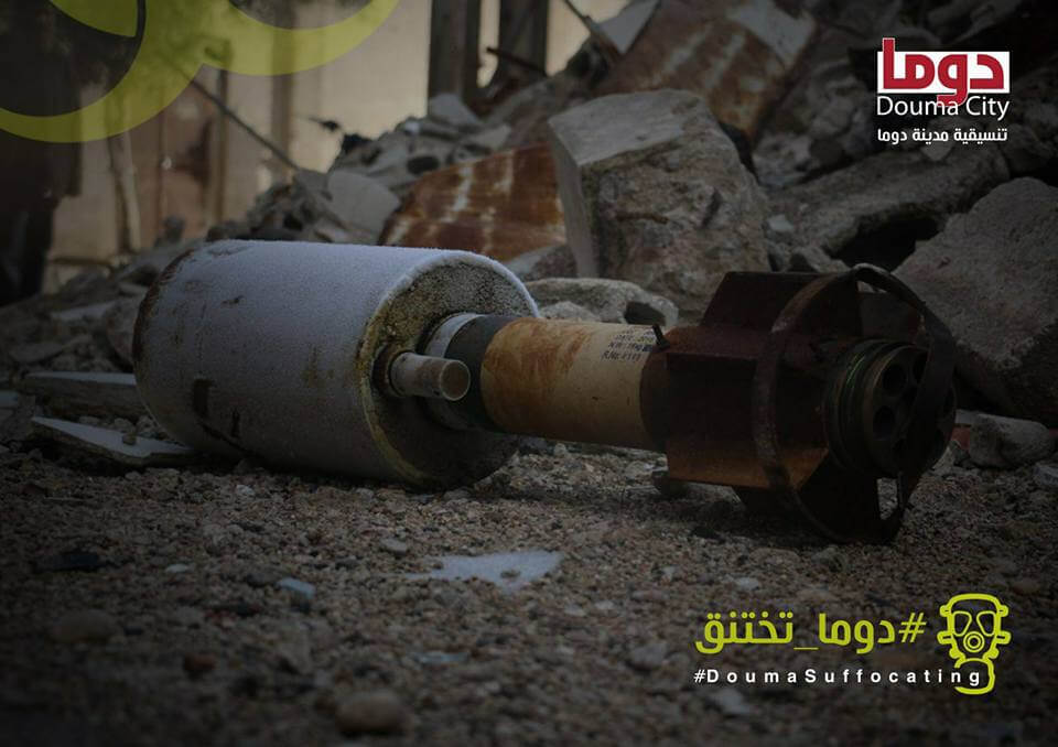 """Photo shows a close-up of a Golan rocket laying among rubble and larger stones. The photo includes two logos: one on the top right corner of the television channel Douma City, and one on the bottom right corner of a hashtag reading, """"Douma Suffocating"""". Both logos are written in English and Arabic. The photo was taken following a chemical attack in Duma in January 2018 and appeared in a Bellingcat report in 2018."""