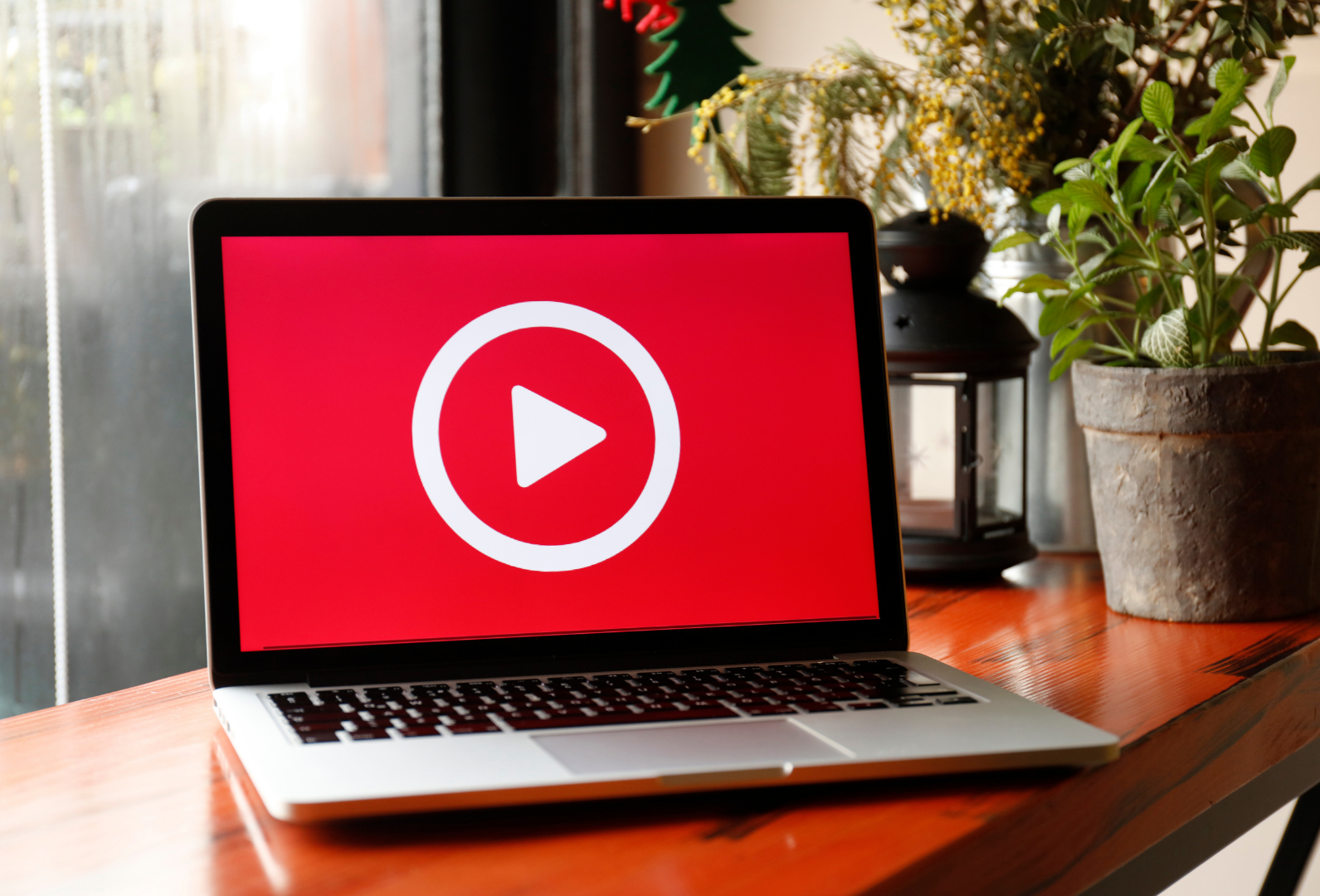 """White circle with a """"Play Video"""" symbol on red background on laptop computer screen"""