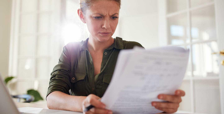 Junge Frau mit Dokumenten am Laptop - Was sagt mir meine erste Renteninformation