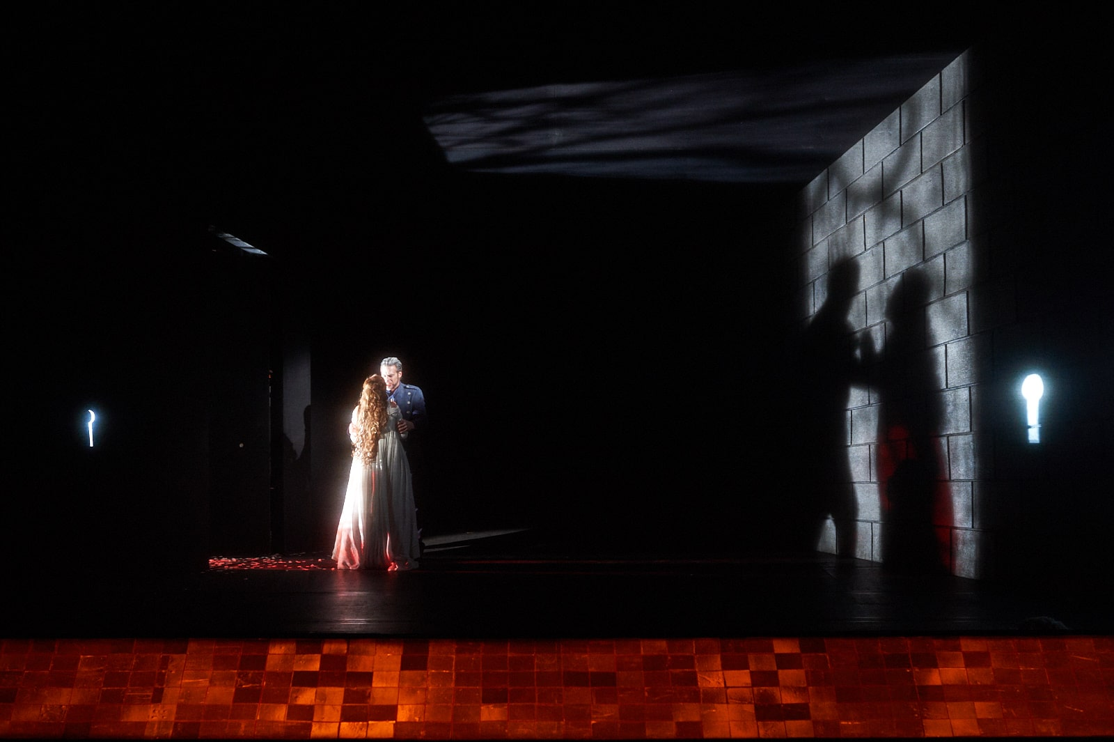 Woman in white dress and man in blue uniform stand clasped, casting shadows on brick wall - shimmering amber tiles in foreground.