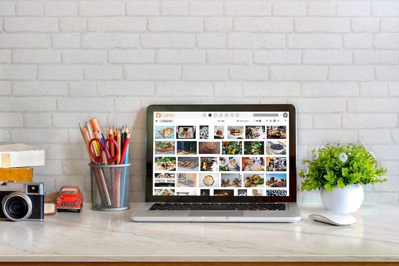 Ein Tisch mit einer Kamera, Stiften, einer Blumenvase und einem Laptop, der Canto's DAM in der Bibliotheksansicht zeigt.