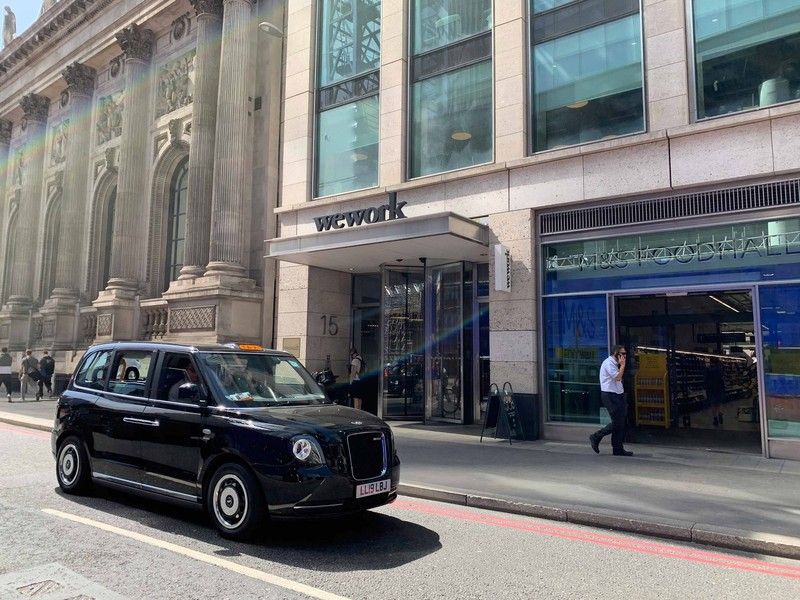 A british taxi parked in front of the WeWork office in London