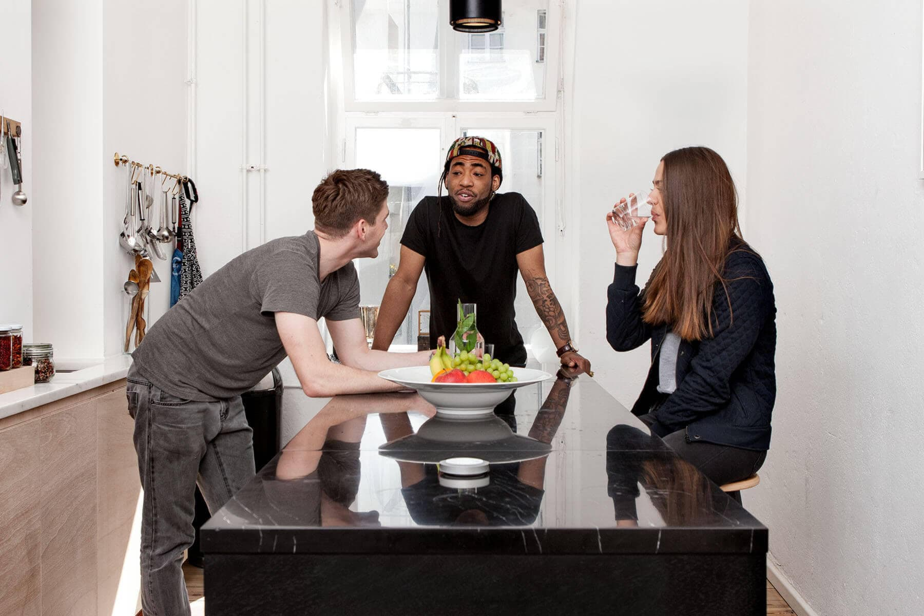 Nuimo grey on a marble kitchen table in a design apartment with 3 stylish people in the background