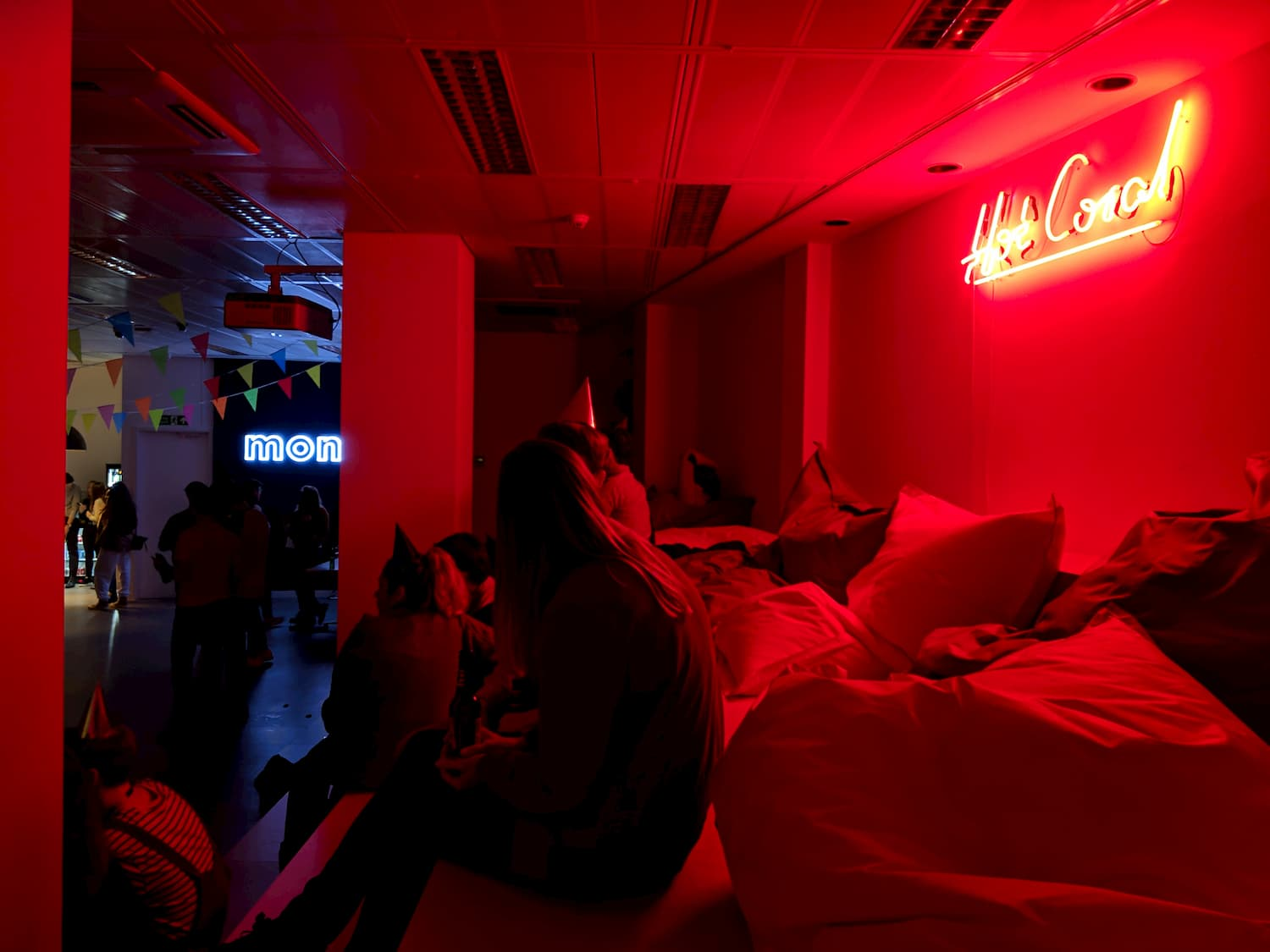 On the right wall a neon sign reads 'Hot Coral' and is projecting a pink glow onto people sat wearing party hats