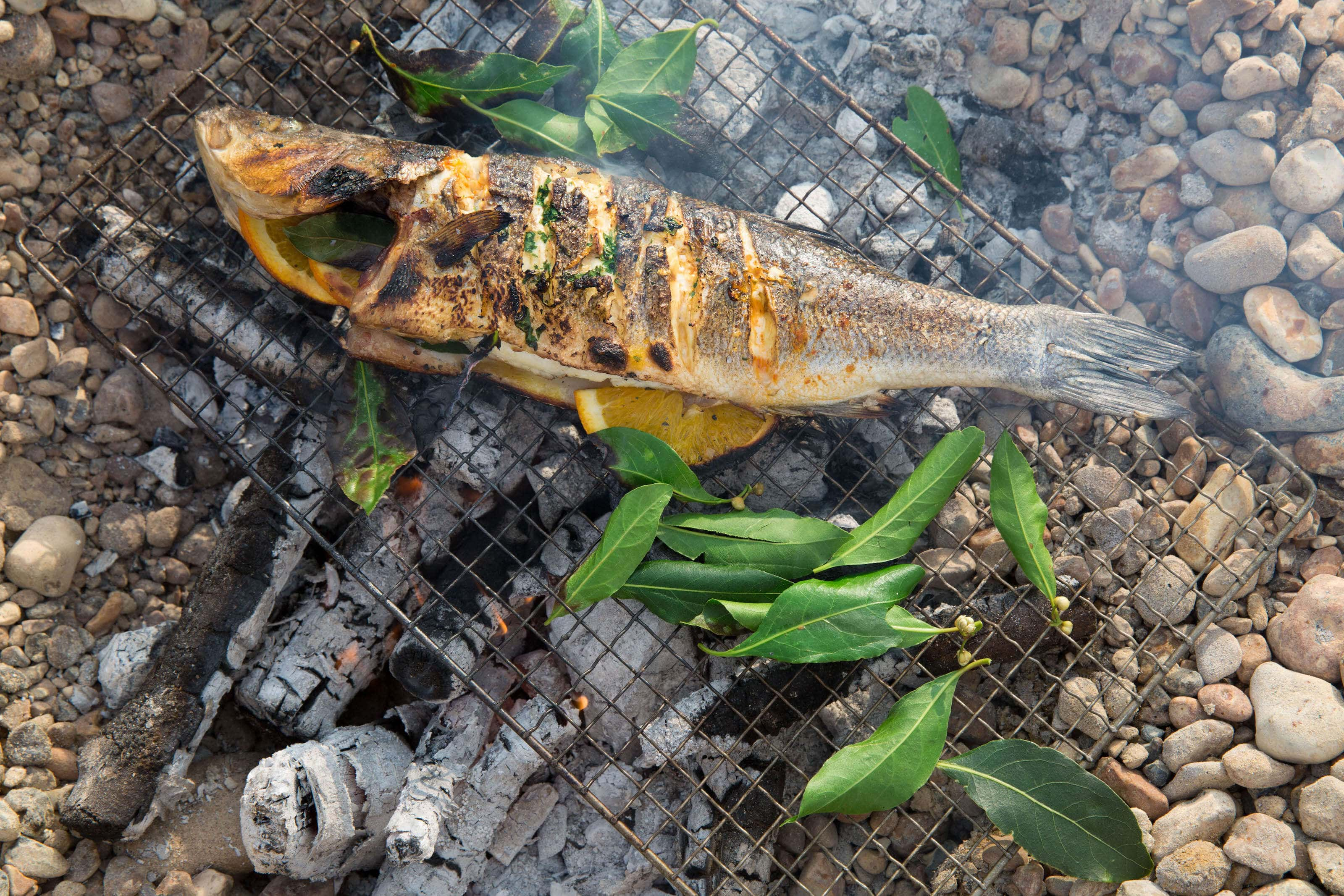 Seabass cooking on the bbq with bay leaves.