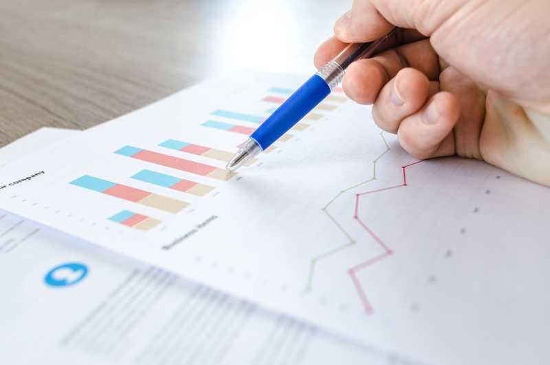 close up of hand with pen reviewing data in charts and graphs