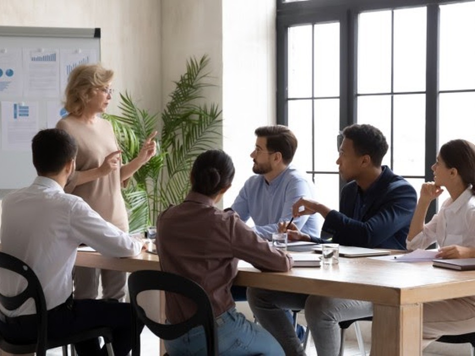 A chief learning officer develops an action plan with five educators seated around a conference table.