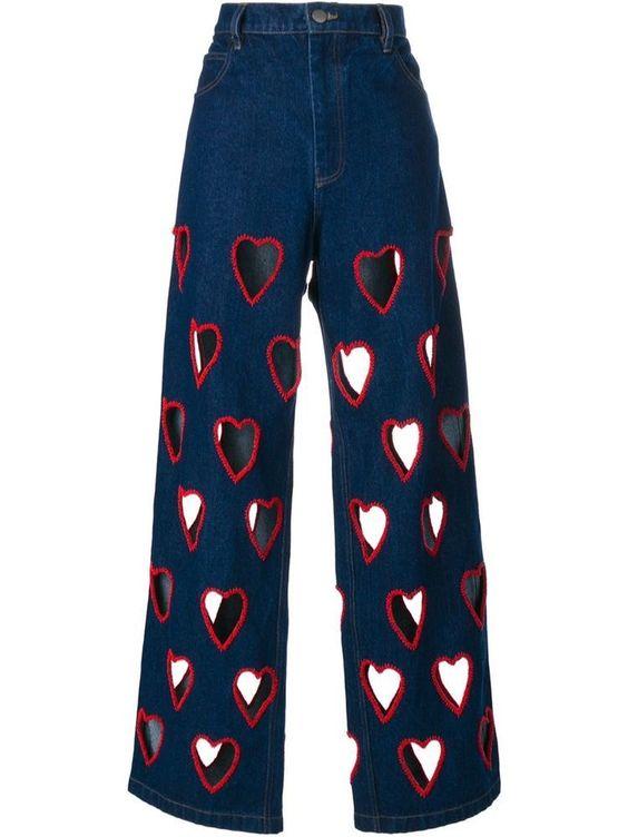 Jean évasé avec des trous en forme de coeurs sur la longueur de la jambe surlignés d'un fil rouge