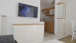 Andere Wohnzimmeransicht mit Fernseher, Sicht auf Küche und Kommode