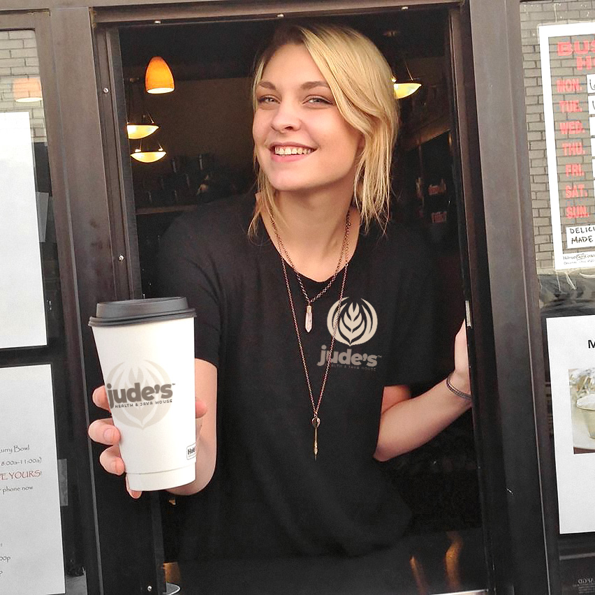 A barista in the drive thru window, offering a cup of Jude's coffee