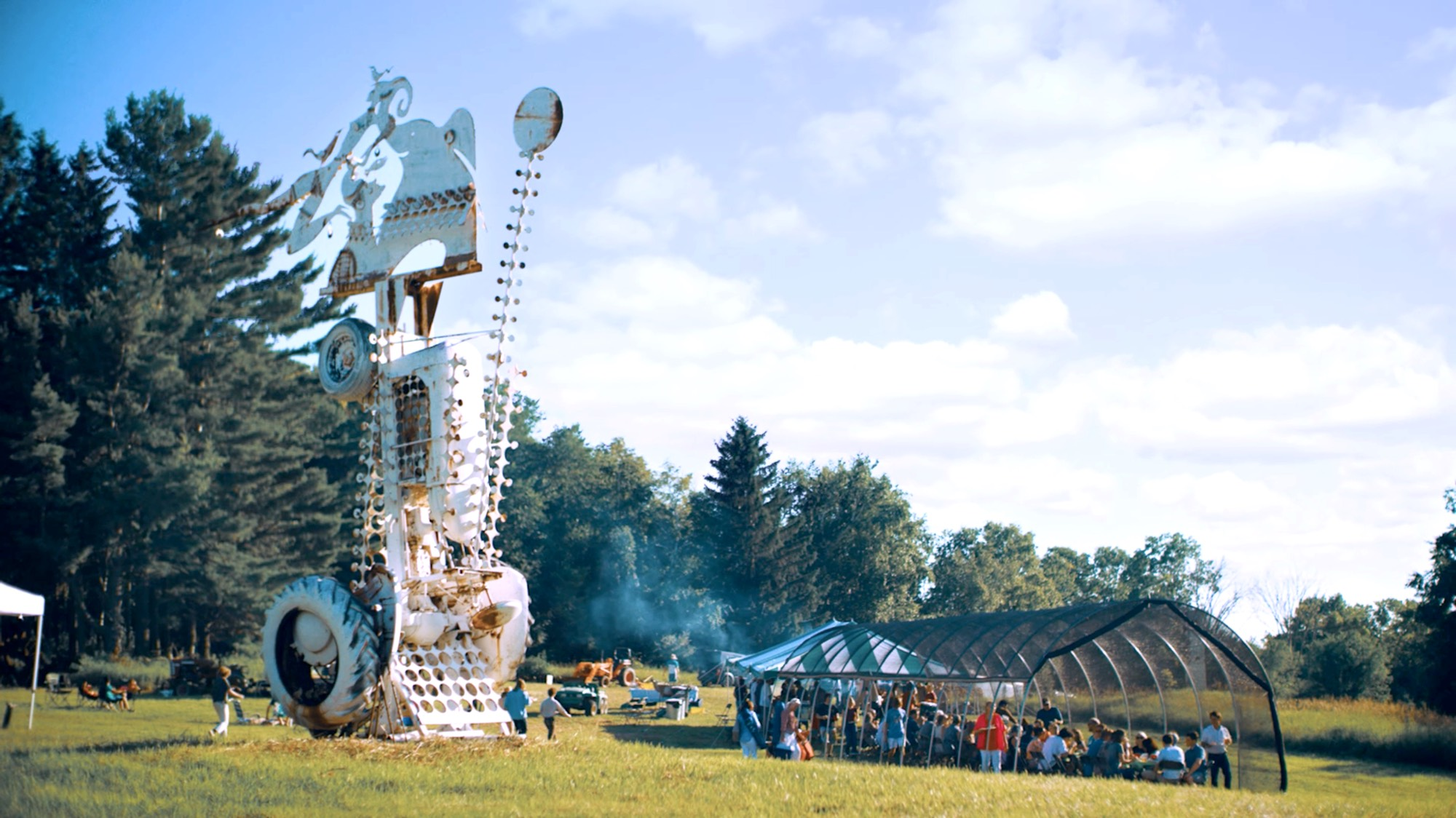 A white sculpture made out of tractor parts towers next to a tent in which festivalgoers are eating dinner.