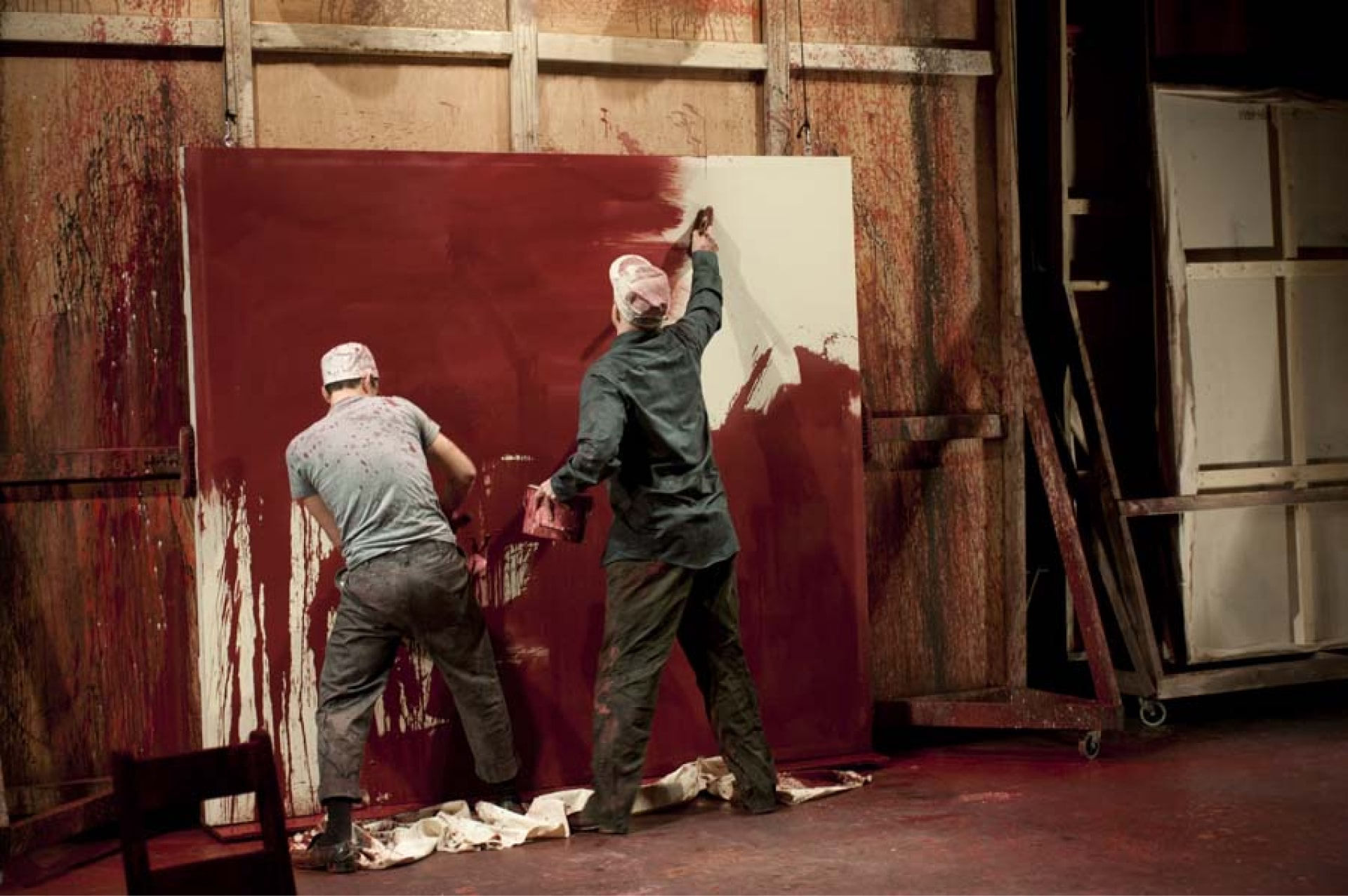 Two men smear red paint on white canvas leaning against wooden wall.