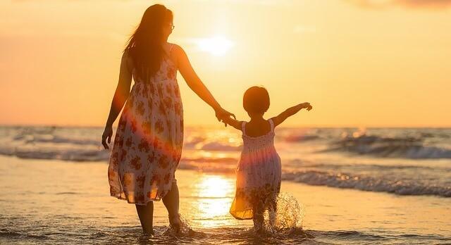 foto de mãe e filha na praia ao por do sol