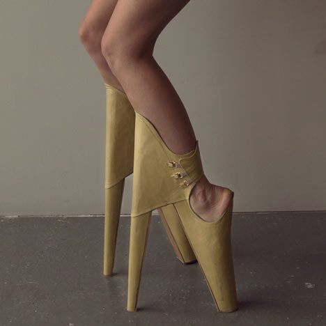 "close up shot of a woman in leather ""heels."" The shoes have the higher heel in front, braced by the front of the calf, so the wearer must bend at an awkward angle to wear them."