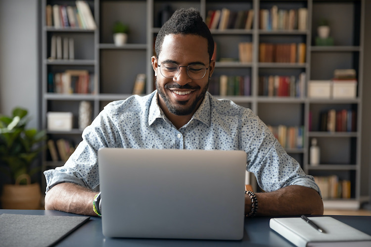 A smiling man using a laptop with a pen and pad by his side.