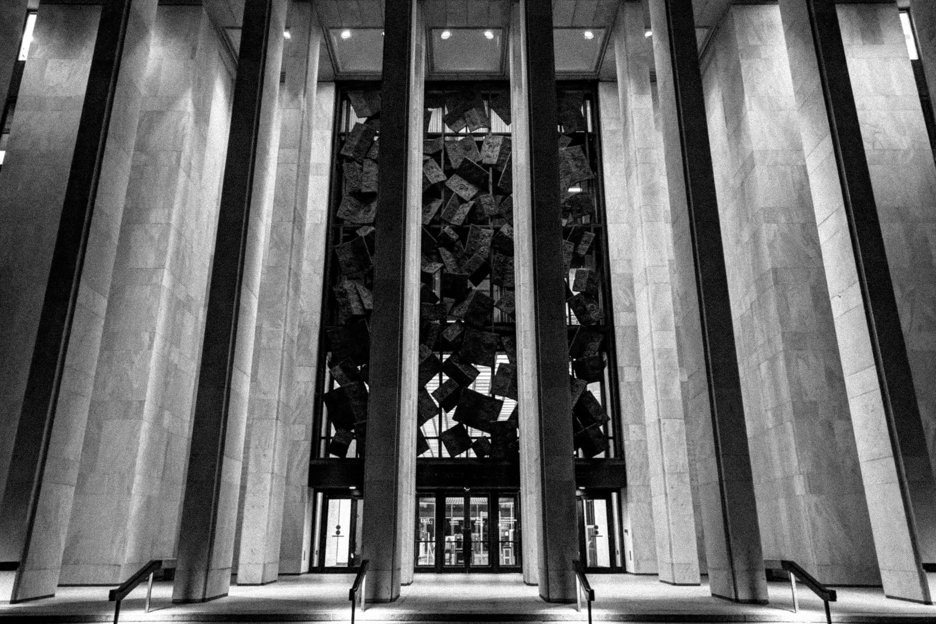 A black-and-white photograph of the Library of Congress annex at night.