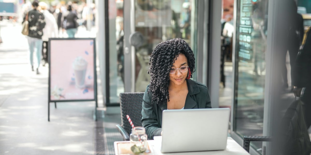 A tech employee works remotely on her laptop sitting outside a cafe, with a drink beside them