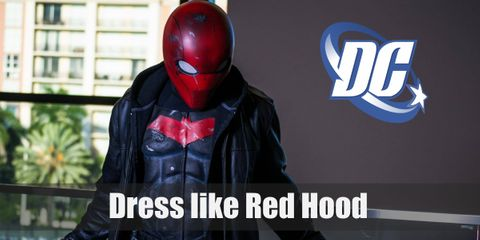 Red Hood's signature look includes a black outfit with a red band on the chest, a brown jacket, gray boots, and a red full-head mask.