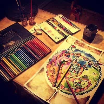 Μολύβια διαφορετικών χρωμάτων και ζωγραφισμένο χαρτί πάνω σε τραπέζι.
