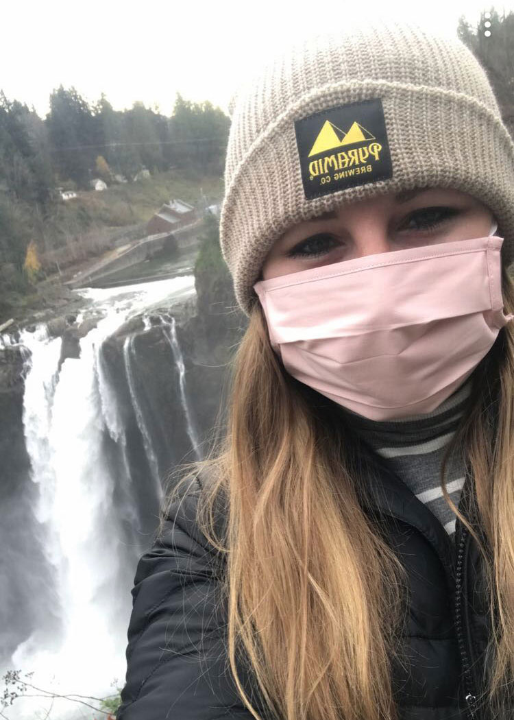 selfie of Lexi Baasch in front of the Snoqualmie Falls. She is wearing a Pyramid Brewing beanie and a face mask.