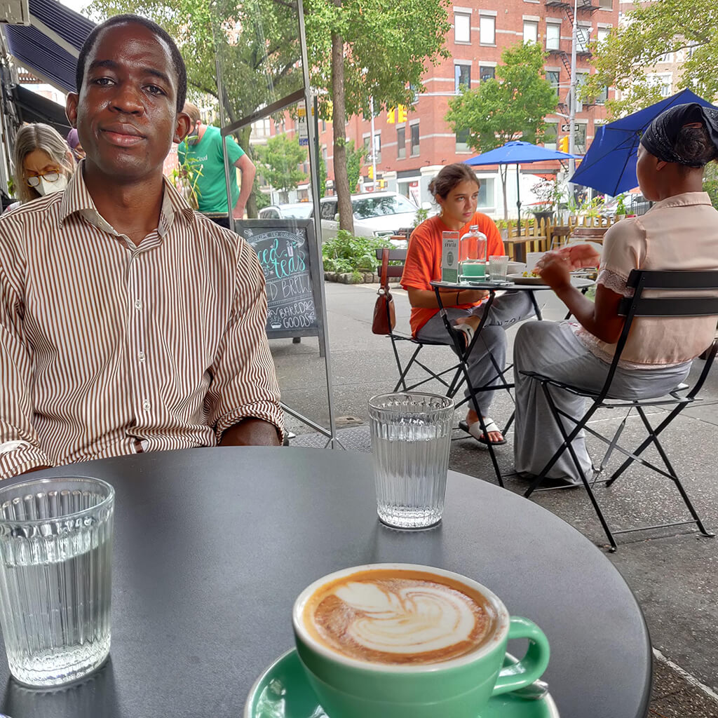 Man at table on sidewalk café with cup of coffee