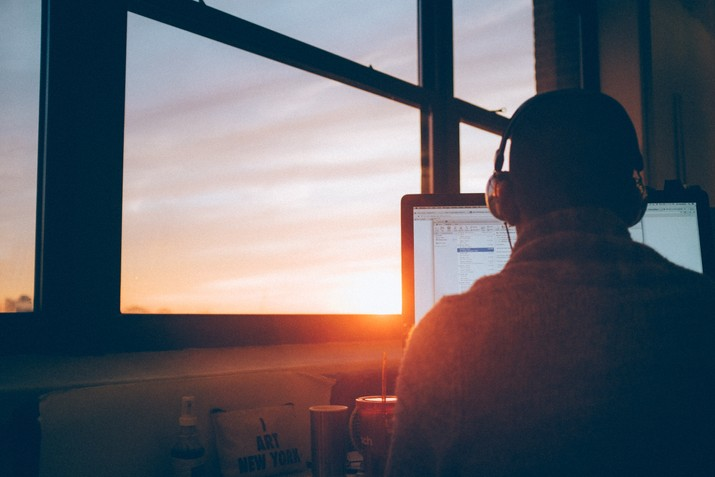 man on computer with sunset in the background