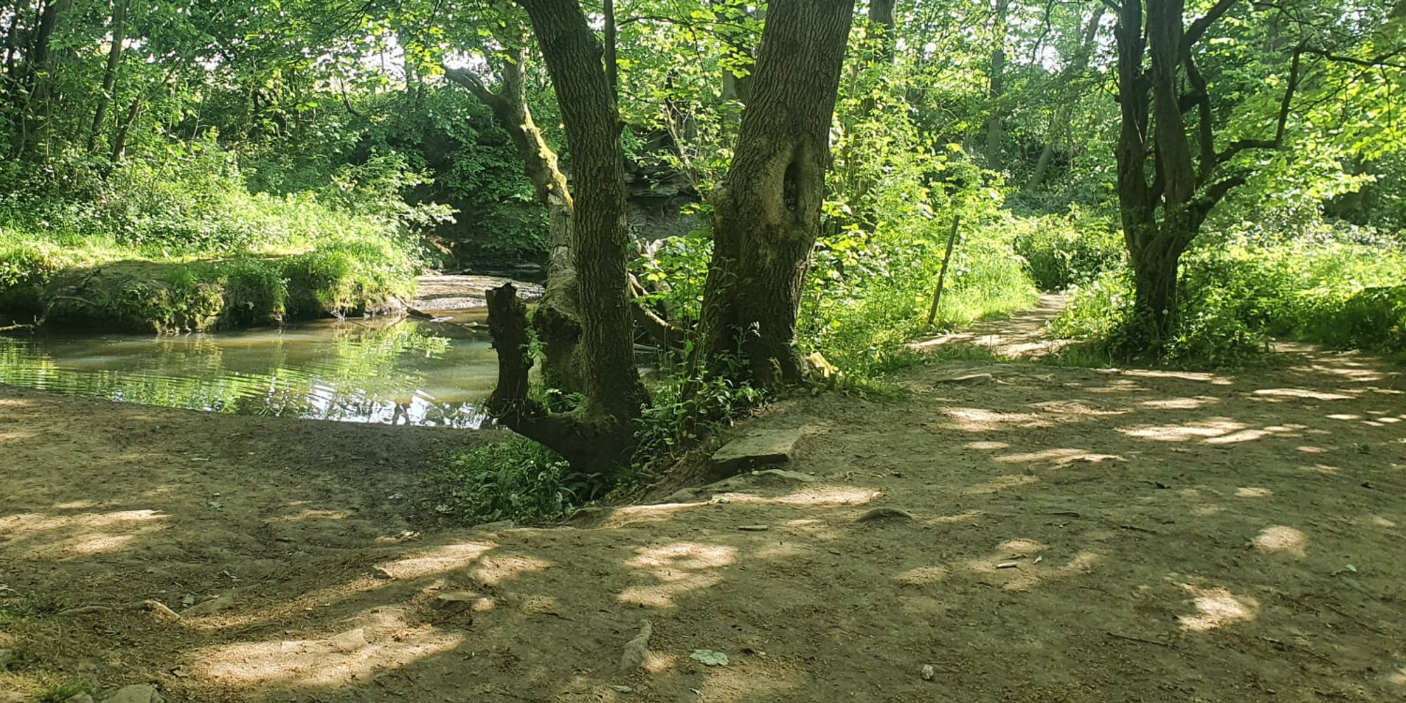 A dry path alongside a stream at Post Hill