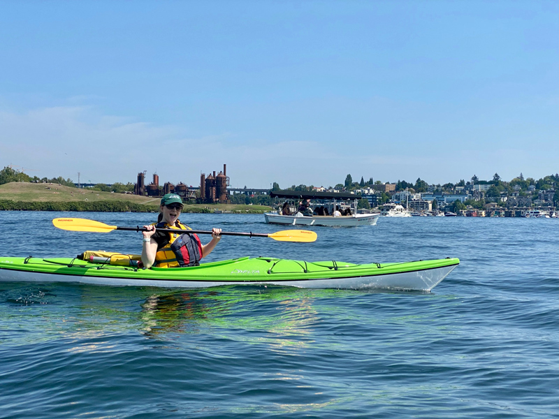 Me sitting in a neon-green kayak, holding my paddle aloft with an excited expression. I am in the middle of a lake with a cityscape behind me.