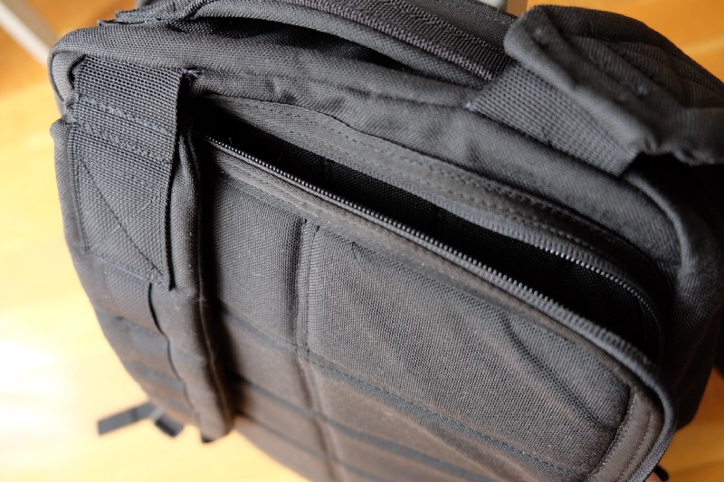 Laptop compartment is behind the straps. It's more safer, but harder to get in and out your laptop