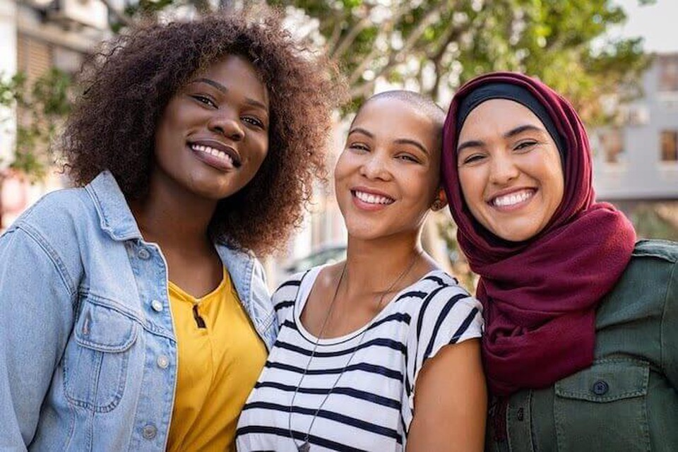 Three young multiethnic women serve as one example of allyship.