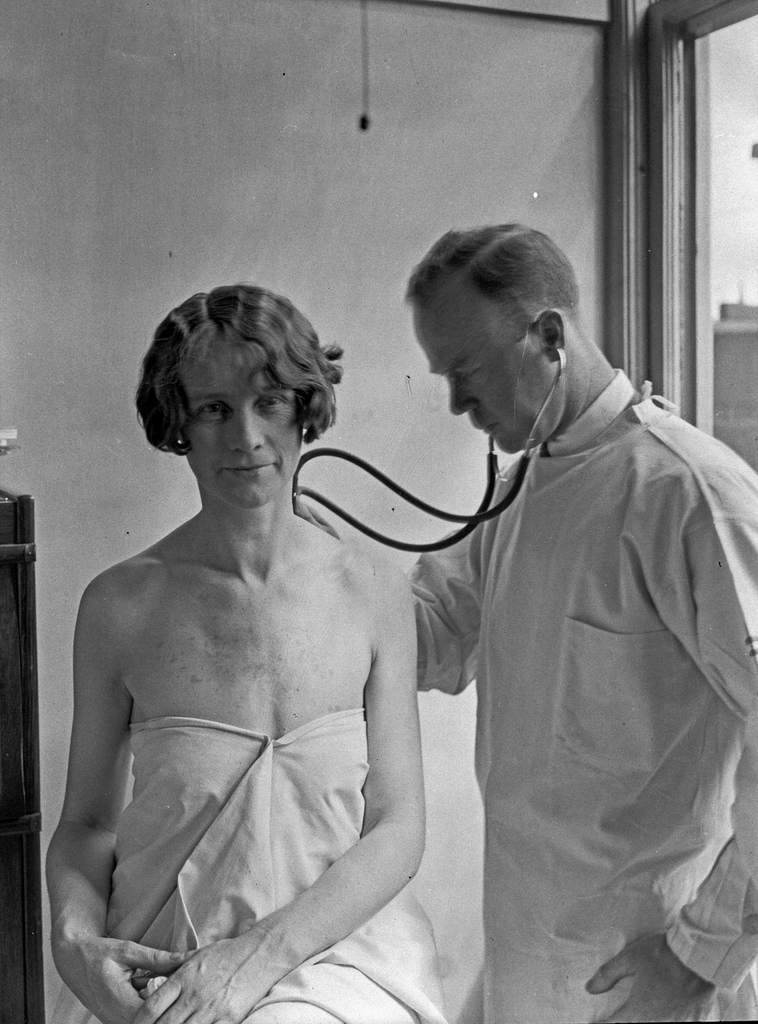 A back and white photo of a woman patient and a male doctor, likely from the first half of the 20th century,. The woman sits with a sheet wrapped around her torso, and the dotor listens to her back with a stethoscope.