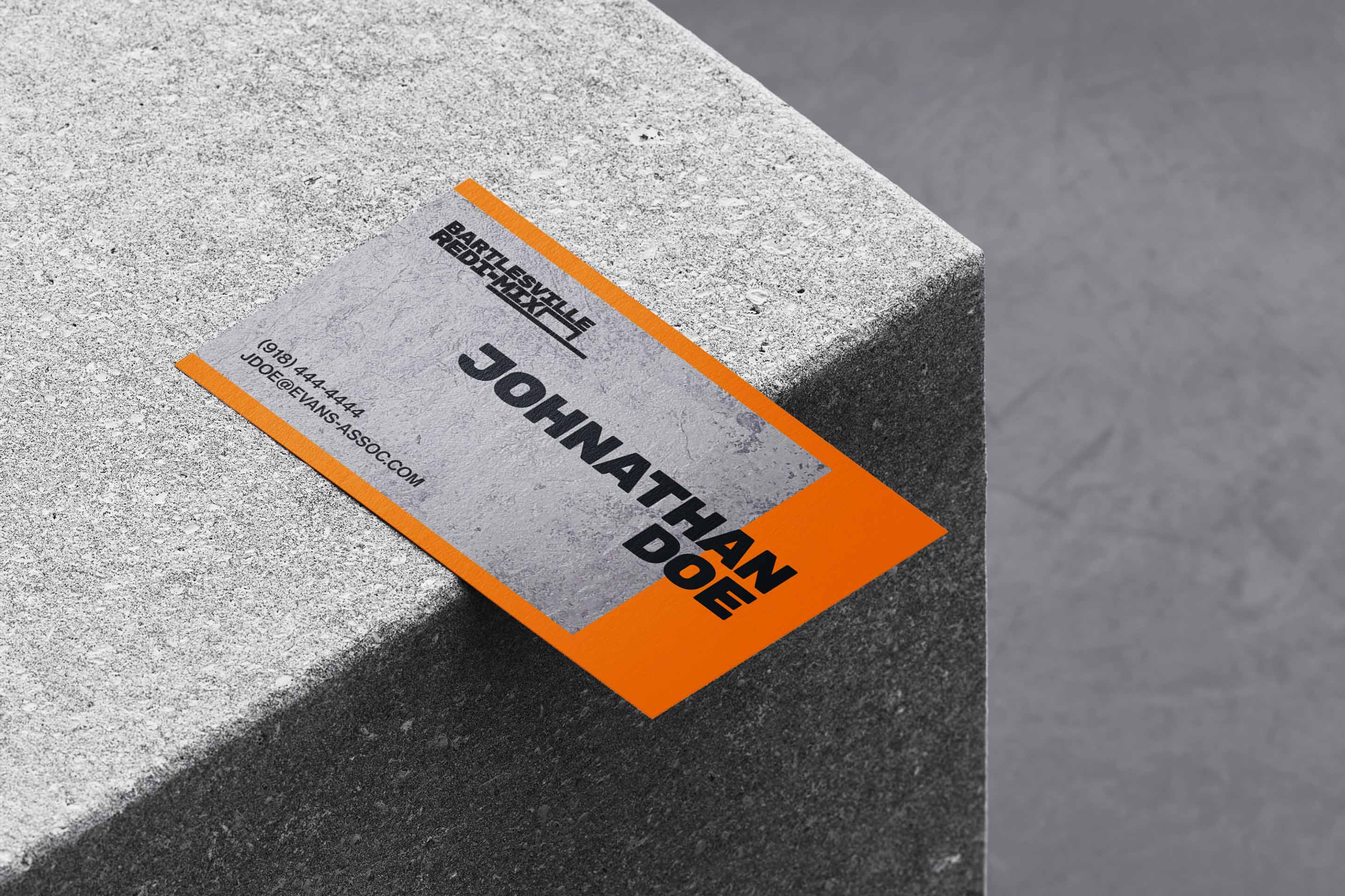 The back side of an orange business card featuring the Bartlesville Redi-Mix logo concept