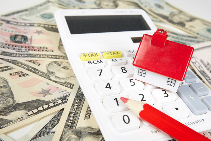 A calculator and a tiny home on top of a bunch of cash.