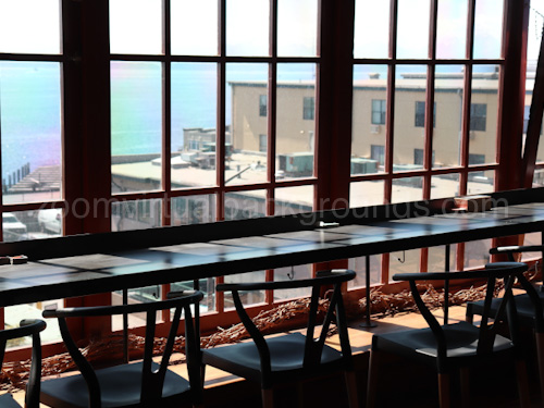 Cafe Virtual Background for Zoom with long table and window looking onto sea view