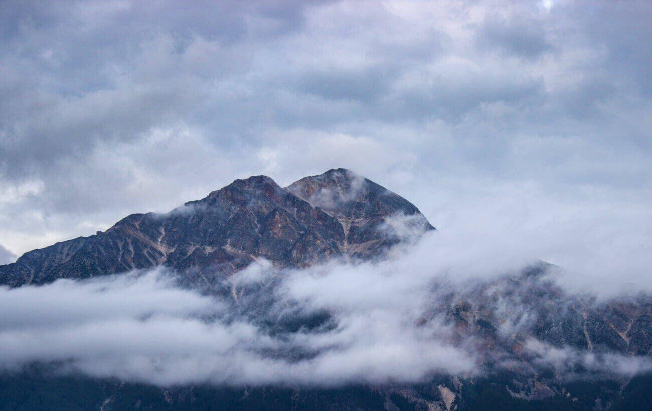 Uma montanha com algumas nuvens cobrindo partes dela