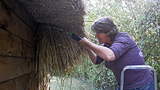 woman thatching a roof