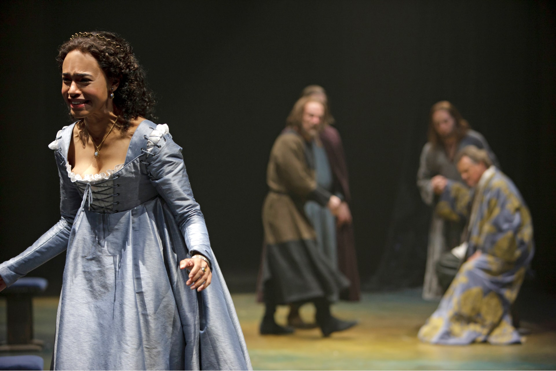 Woman in blue gown stands crying with out-of-focus men in background.