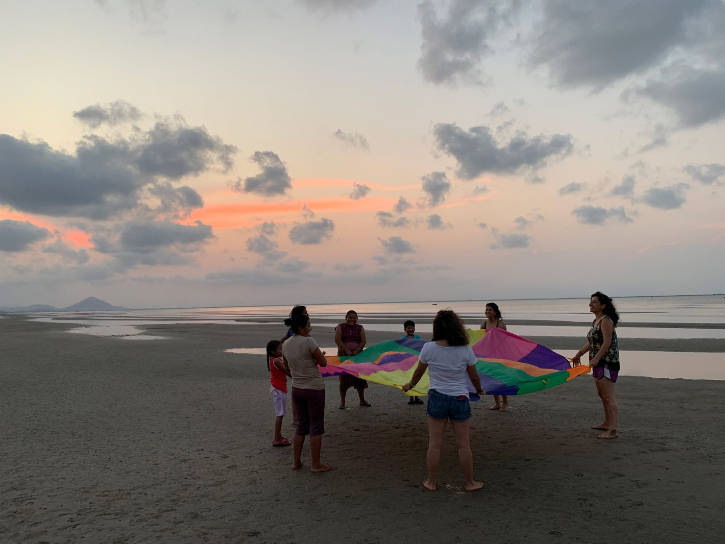 six women and two children stand on the beach at mar muerte holding a multicolored circular sheet