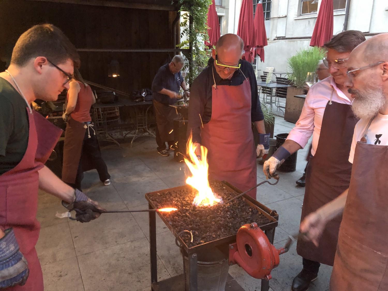 Vier Personen stehen verteilt um ein Kohlefeuer und erhitzen ihr Werkstück zur Bearbeitung.
