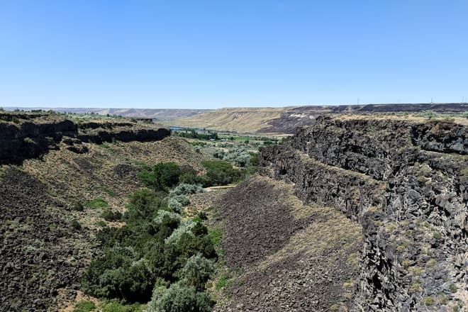 A dense swath of sage, Russian Olives, and native trees cuts across a field of broken basalt boulders at the bottom of a sheer canyon. In the distance is a wide, low desert river valley.