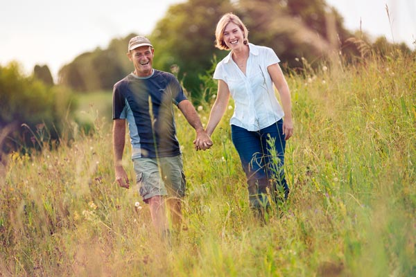 Rory & Sue Brighton holding hands walking through a field.