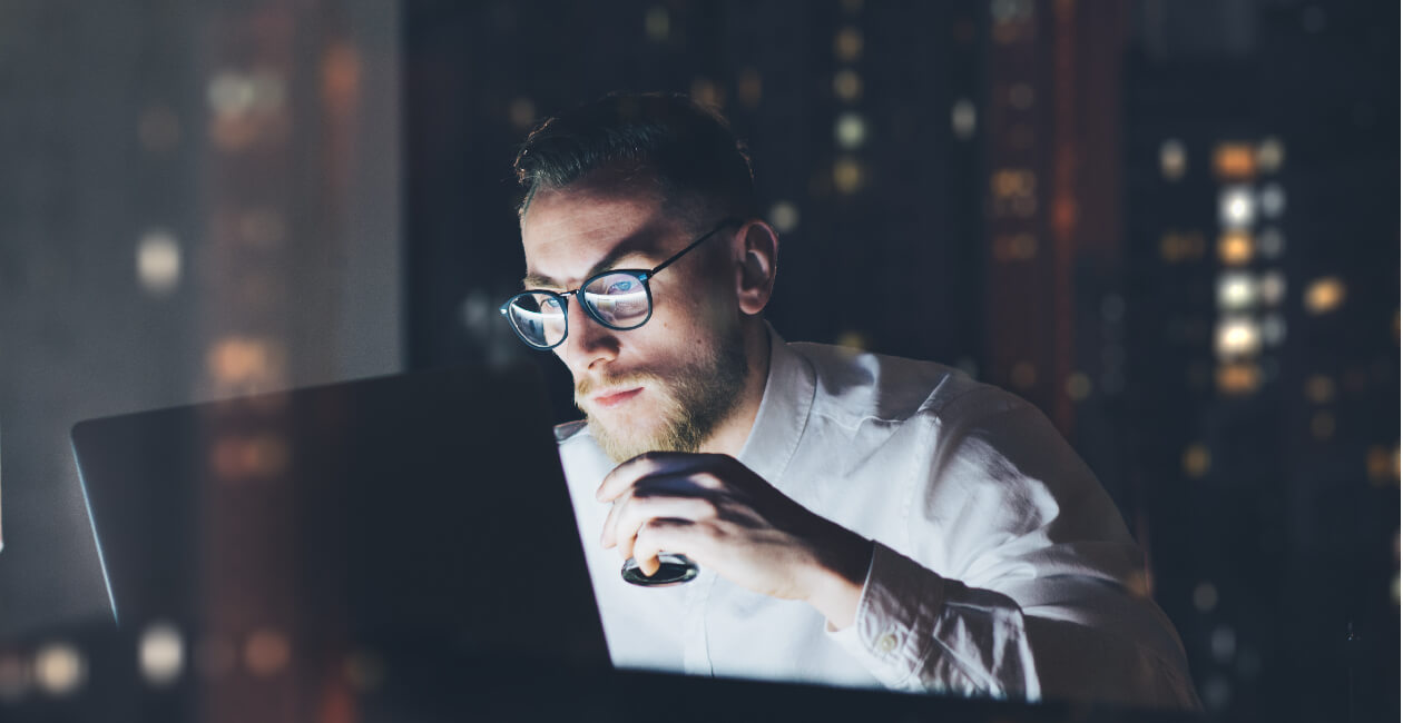 Senior UX recruiter staring at a laptop screen in his office at night time