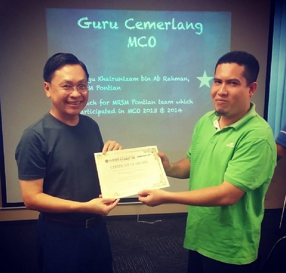 Mr Mark Chang presenting Cikgu Khairunizam from MRSM Pontian with the 'Guru Cemerlang MCO' award.