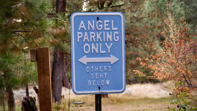 A sign says 'Trail Angel Parking, others sent below'