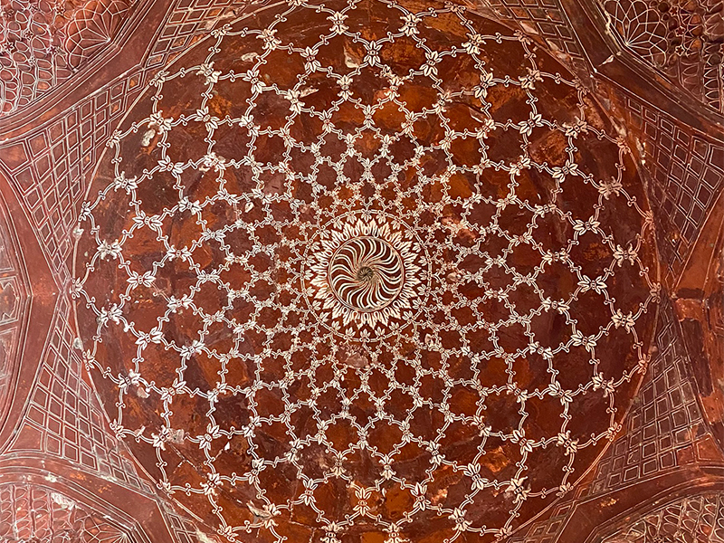 A terracotta mosque ceiling with an intricate white design inside a large circle