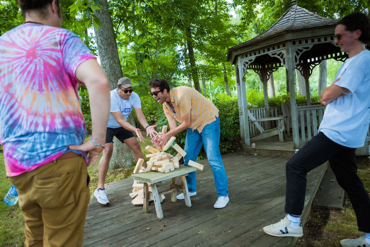 Chris W. and Jesse attempting to catch a Jenga tower. Jenga tower is mid-collapse. Chapman and Matt look on
