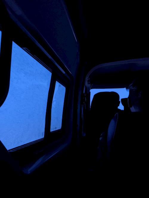 A dark interior of a van with shadows, with snow outside