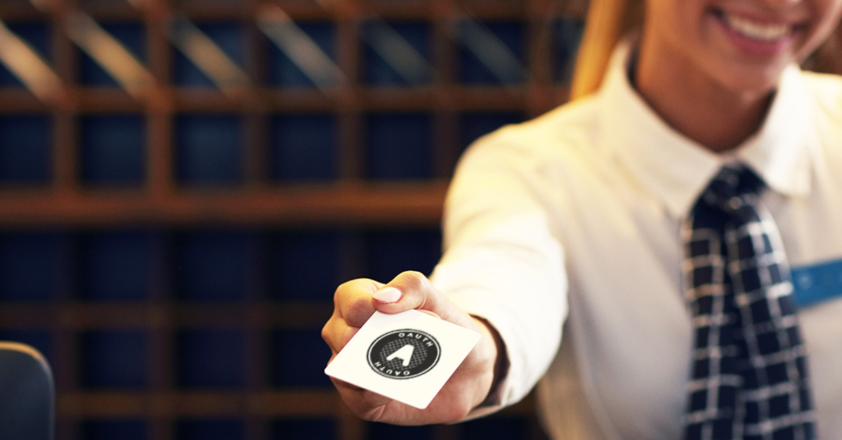 Photo of a hotel desk clerk handing a hotel key to the viewer